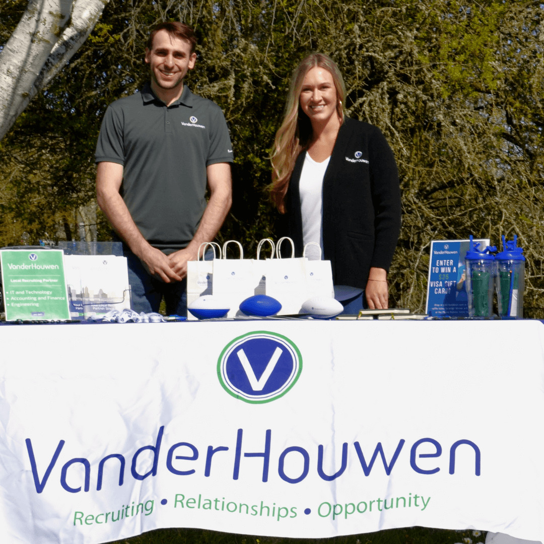 man and woman standing outdoors at an event display table with VanderHouwen on the front banner