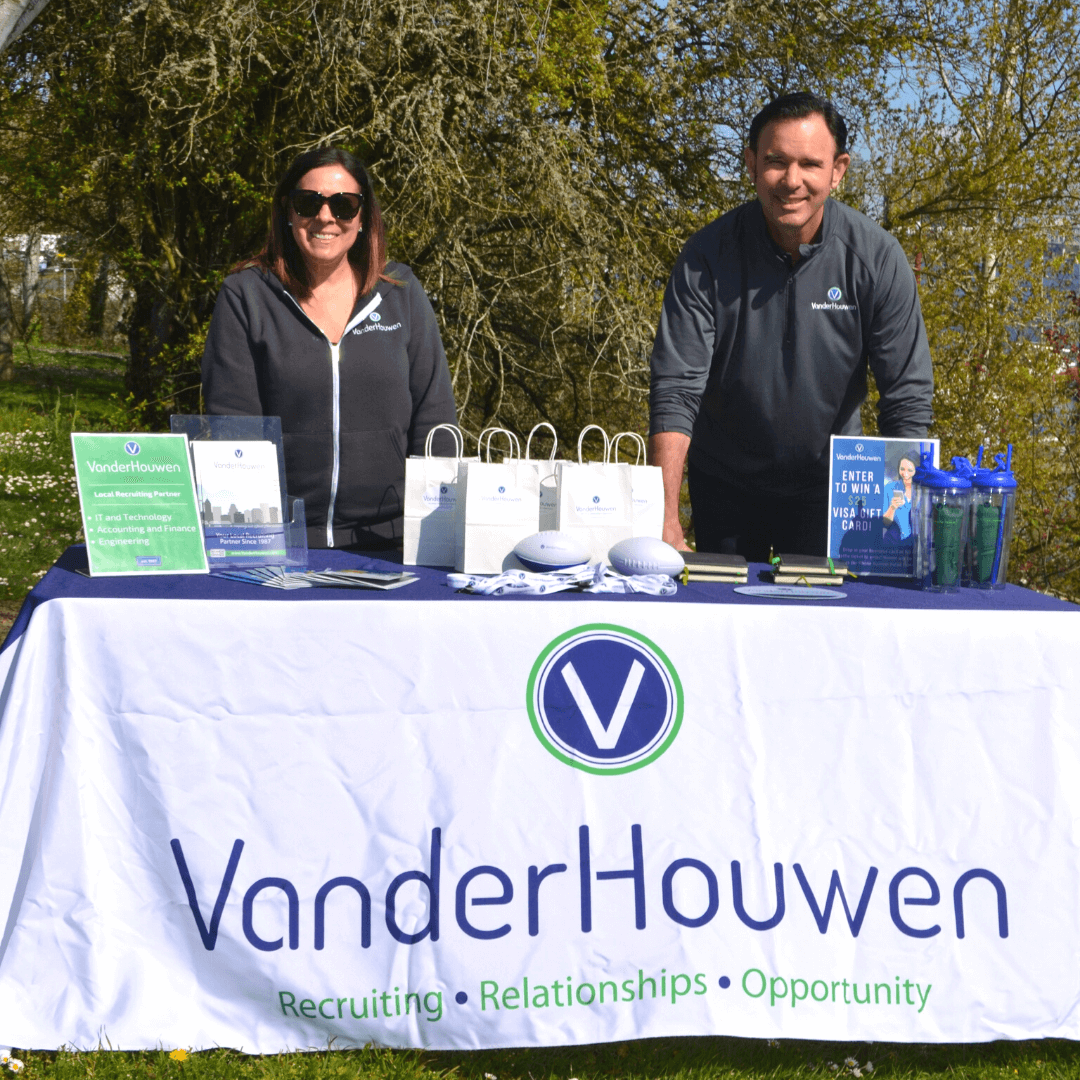 man and woman standing behind VanderHouwen themed event table with gift bags and branded swag on the table