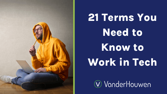 21 Terms You Need to Know to Work in Tech | man in yellow hoodie sitting on the floor with a laptop in his lap and a pencil to his mouth, thinking.